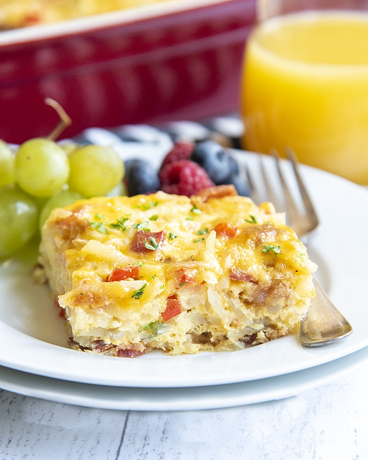 A piece of breakfast casserole with hashbrowns and eggs and cheese on a white plate with grapes and berries on the plate, and a cup of juice behind it.