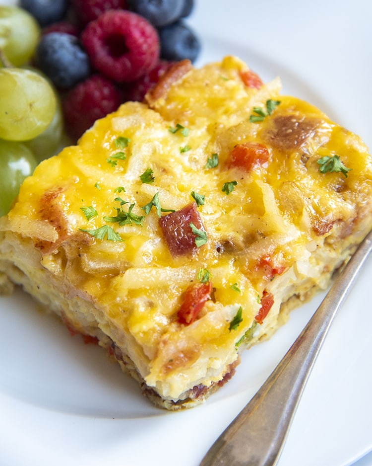 A piece of a savory breakfast casserole on a white plate, with grapes and fresh berries behind it.