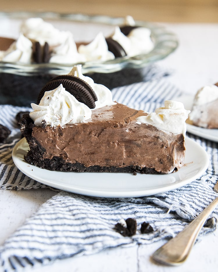 A side shot of a slice of chocolate cream pie. It has an Oreo crust and is topped with whipped cream rosettes.