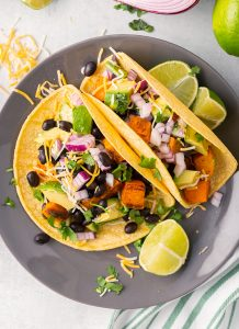 Two corn tortillas filled with sweet potatoes, black beans, red onion, avocado and cilantro.