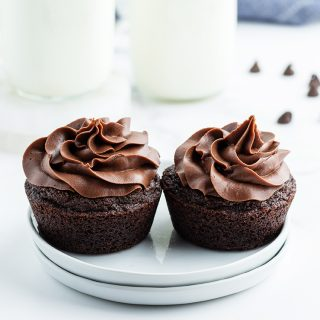 Two chocolate cupcakes with chocolate frosting on small white plates. There are bottles of milk behind them.