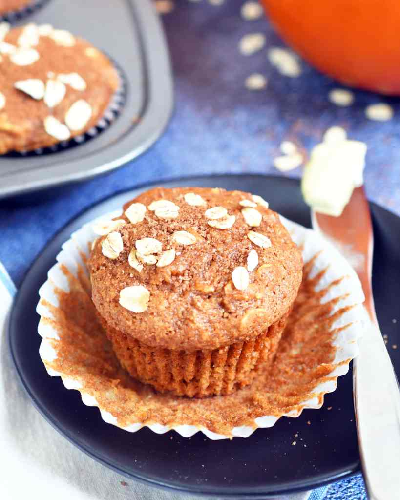 pumpkin oat muffin in a open muffin liner on a brown plate along side a butter knife with butter
