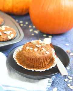 pumpkin oat muffin in an open paper liner on a brown plate along side a butter knife with butter, orange pumpkin and muffin tin in background