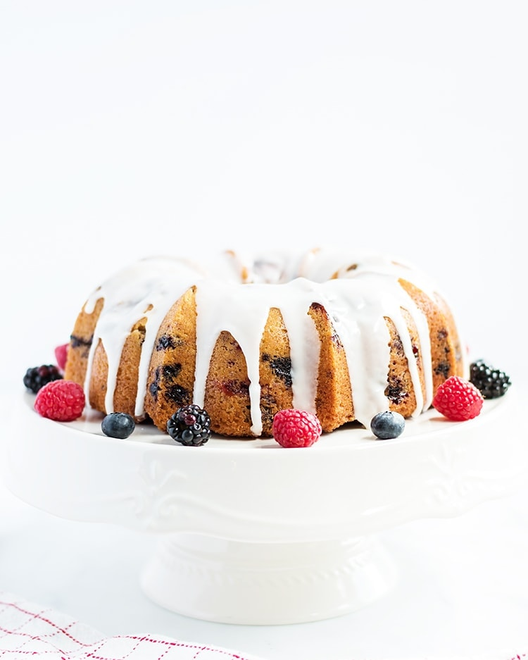 Lemon Berry Bundt Cake with a lemon glaze on a white cake stand with fresh berries on the side