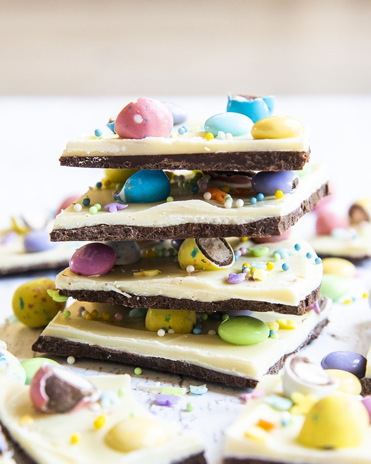 A stack of 4 pieces of Easter bark, with layers of chocolate, white chocolate, and topped with Easter candies.