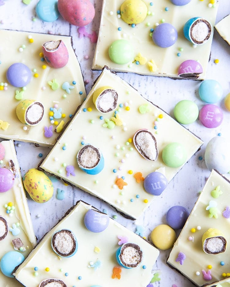 A spread of chocolate bark, topped with white chocolate, covered in chopped up malted eggs, m&ms, and pastel sprinkles.