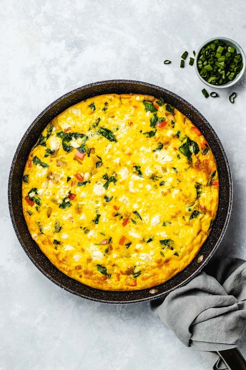 A frittata full of spinach, and potatos, and you can see some pieces of red pepper.