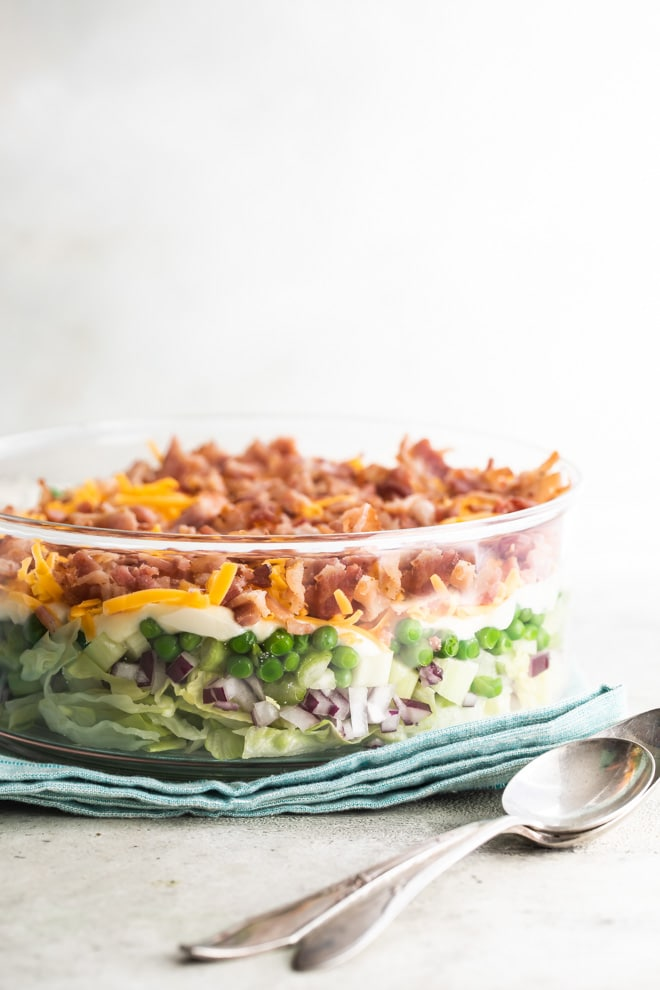 A 7 layer salad in a clear bowl so you can see all the layers including lettuce, peas, bacon, and cheese.