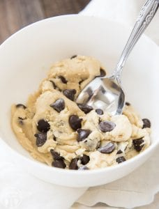 A small bowl full of edible cookie dough with lots of chocolate chips. There is a spoon in the bowl.