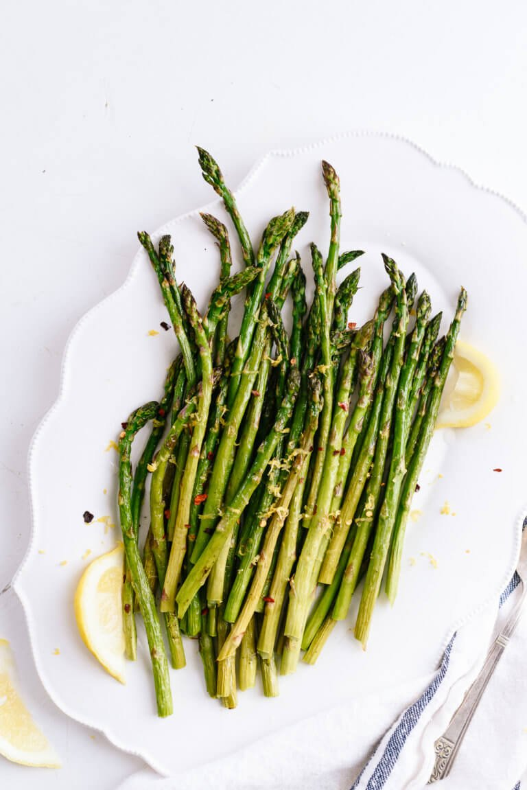 Roasted Asparagus on a white plate topped with red pepper flakes and parmesan cheese.