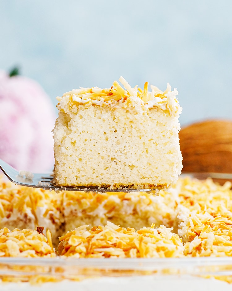 Coconut Cake being pulled out of a pan with a spatula