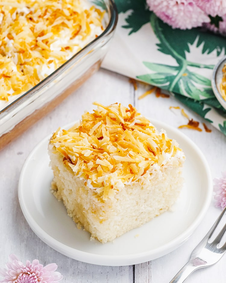 A slice of Coconut Poke Cake topped with toasted coconut on a plate.