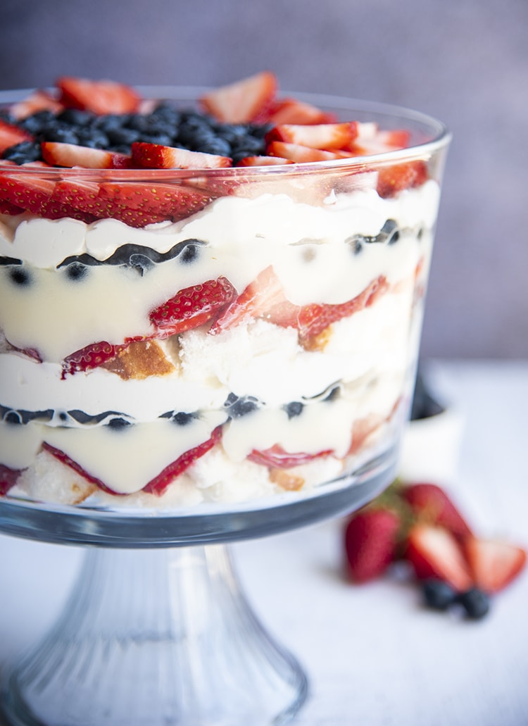 A red white and blue trifle with layers of angel food cake, strawberries, pudding, blueberries, and whipped cream