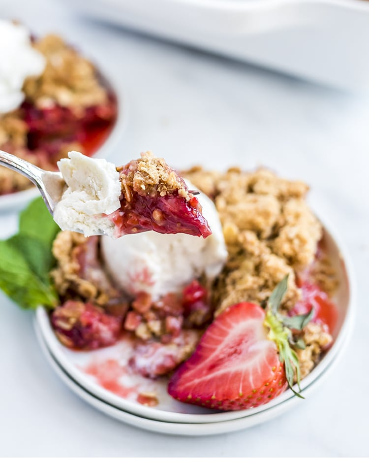 A bite of strawberry rhubarb crumble on a fork