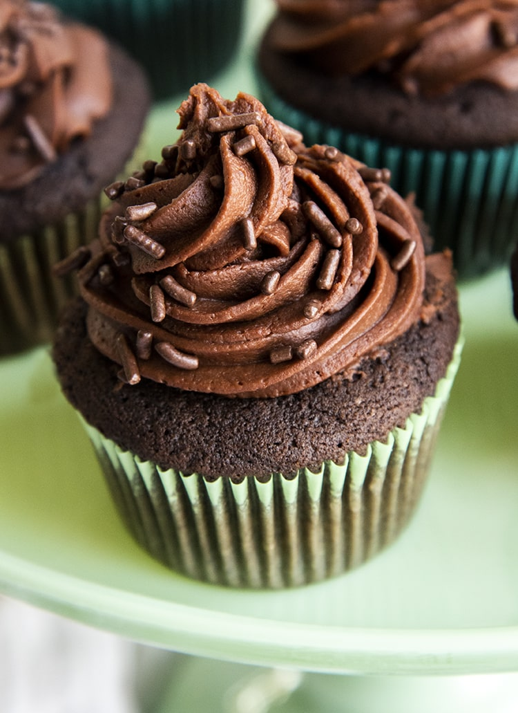 A close up of a chocolate cupcake on a green cake stand.