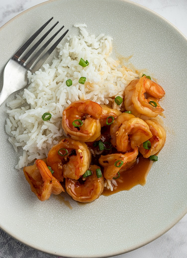 A small grey plate half full of honey glazed shrimp, and the other half full of white rice. They are both sprinkled with sliced green onions.