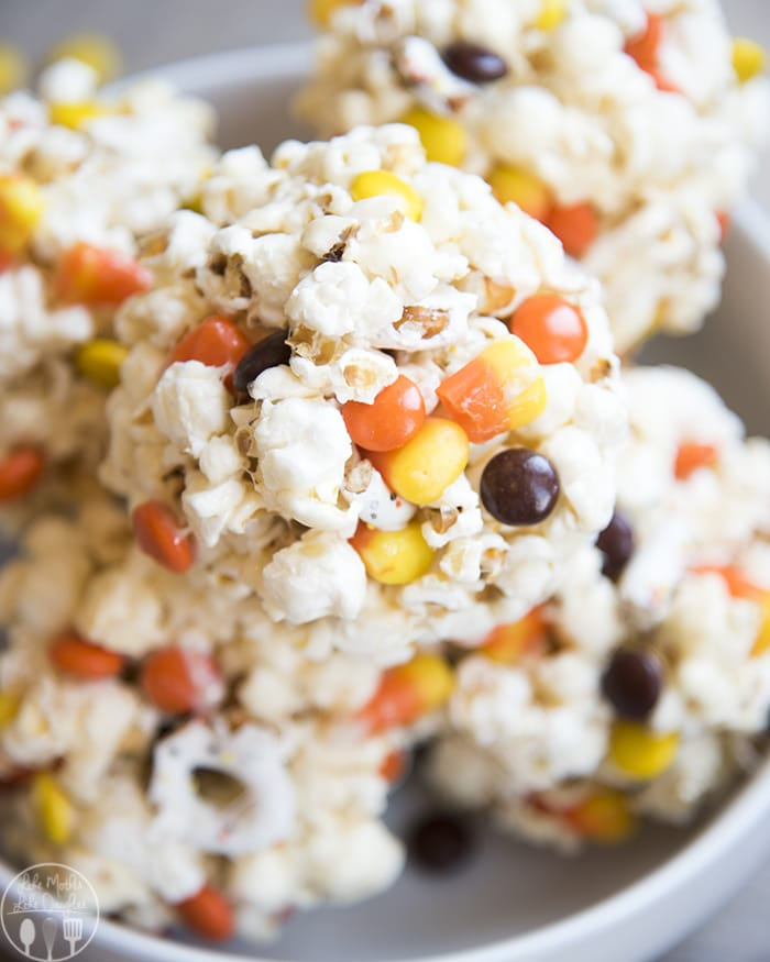 Halloween Popcorn balls with reeses pieces, candy corn, and white chocolate pretzels