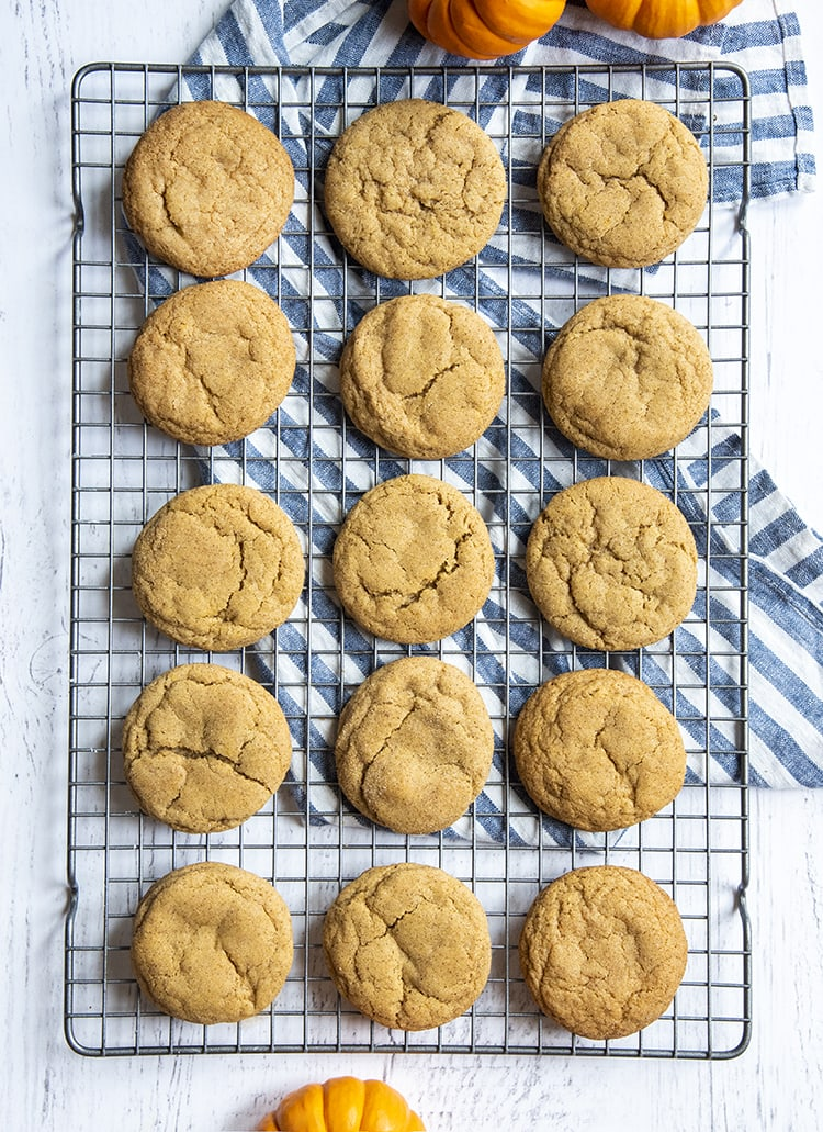 A cooling rack with pumpkin snickerdoodle cookies on it.
