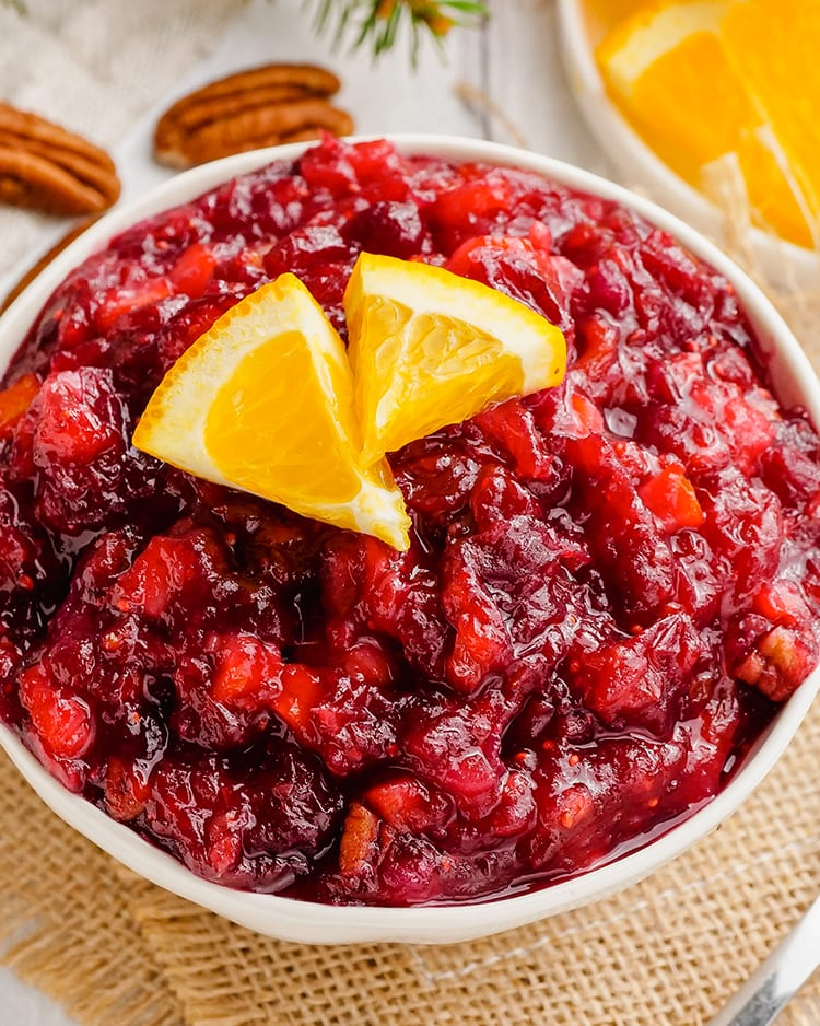 A close up shot of a white bowl full of cranberry orange sauce.