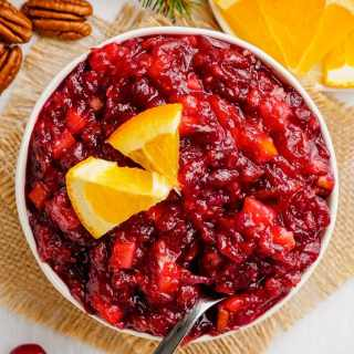 A bowl of cranberry sauce topped with a couple small orange slices with a spoon in the bowl.
