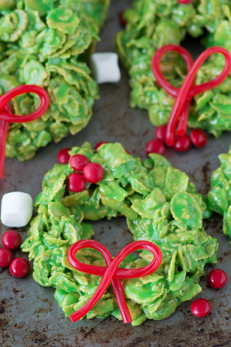Marshmallow Treats made with corn flakes, and colored green and shaped like Christmas wreaths. Topped with cinnamon red hots to look like holly berries on wreath.
