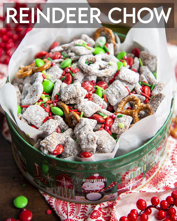 A christmas tin full of Reindeer chow which is muddy buddies with red and green m&ms, and mini pretzels. There is a text overlay over the top of the photo that says Reindeer Chow.