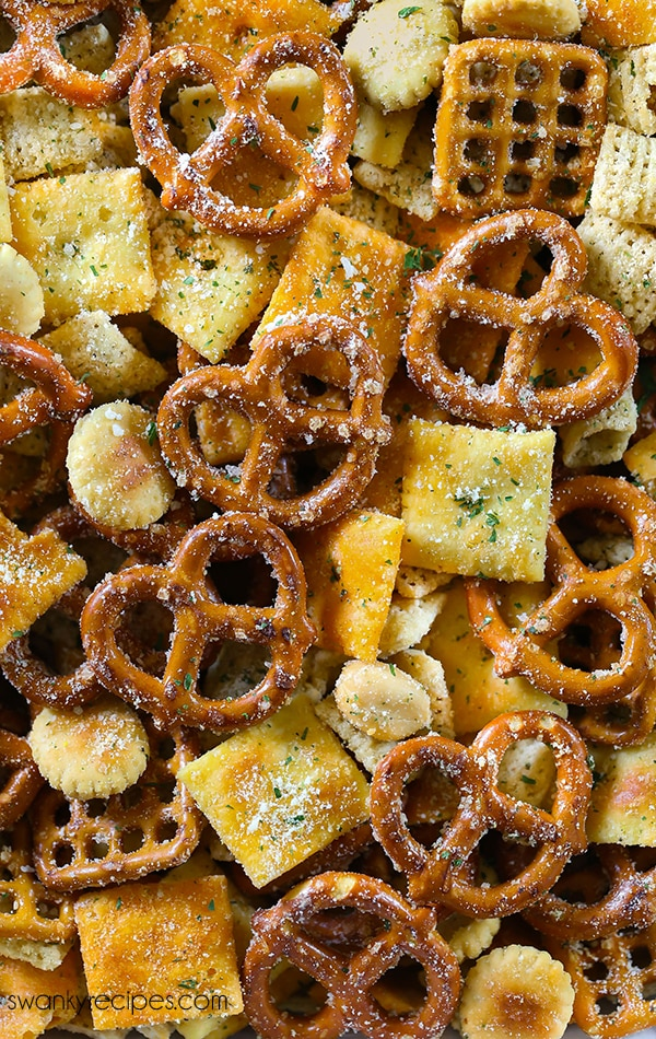 A close up of a snack chex mix coated in ranch seasoning. There are pretzels and small crackers.