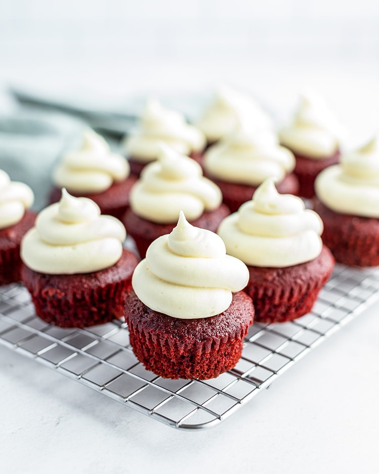 Cream Cheese Frosting on top of red velvet cupcakes in swirls.