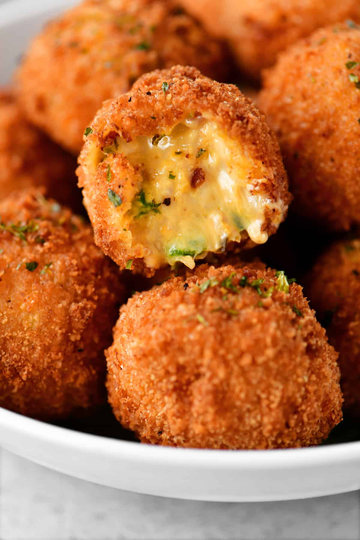A bowl of cheesy bites covered in breading, they look deep fried, and there are pieces of jalapenos and bacon in them.
