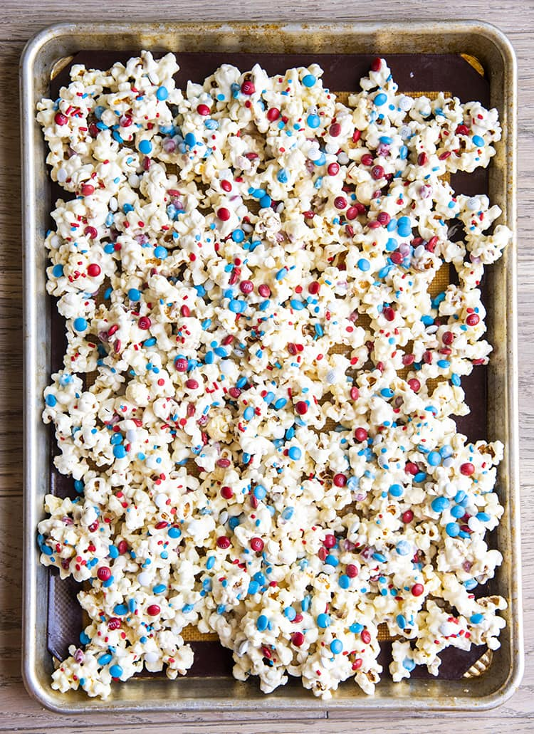 popcorn covered in white chocolate and red white and blue sprinkles and m&ms on a baking tray