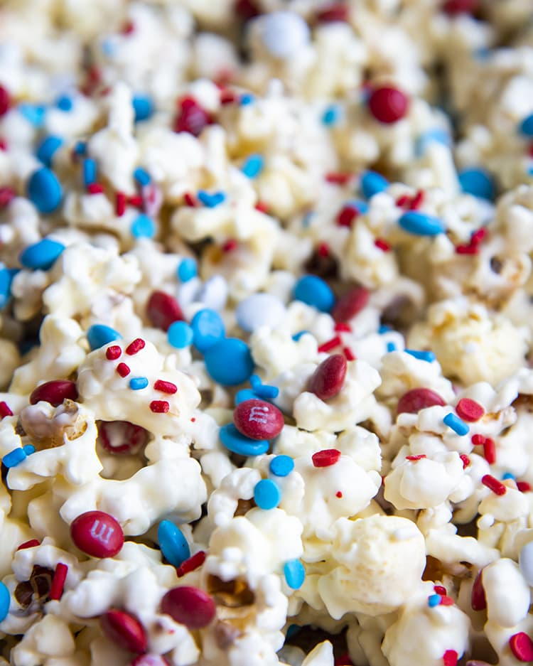 popcorn covered in white chocolate and red white and blue sprinkles and m&ms