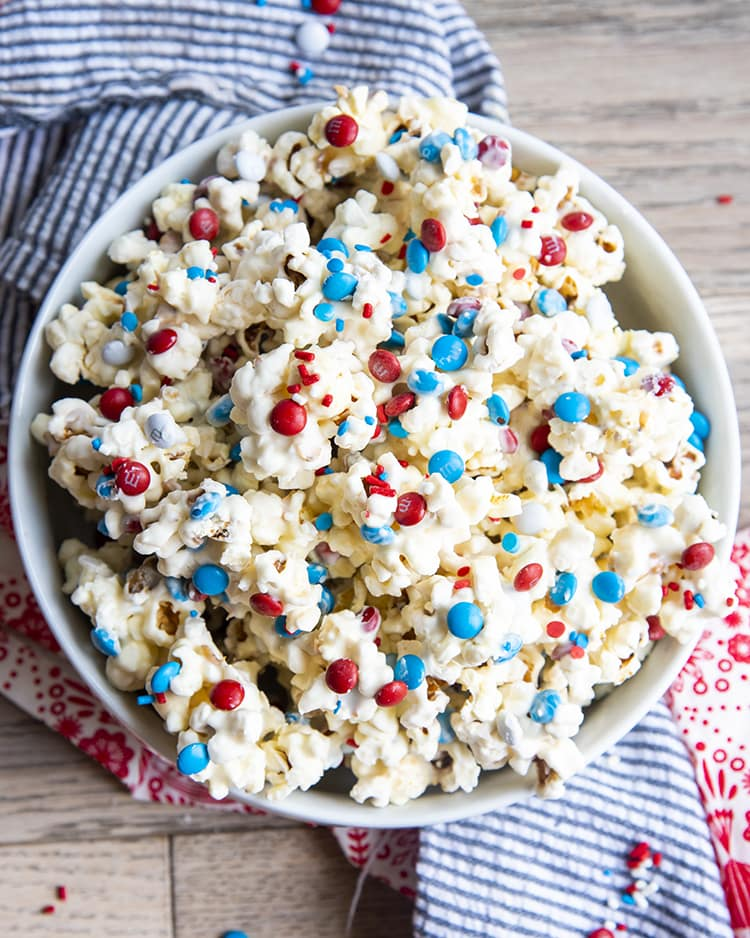 An overhead shot of white Chocolate Popcorn with red white and blue m&ms and sprinkles in a white bowl