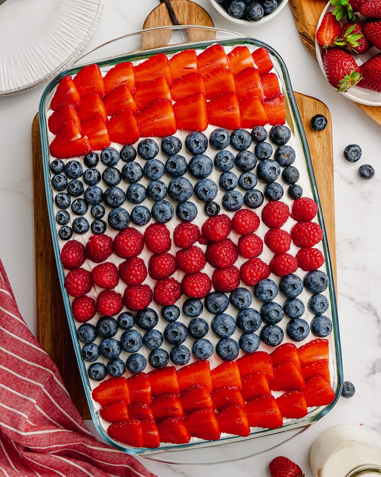 A cake in a pan with stripes of strawberries, blueberries and raspberries.