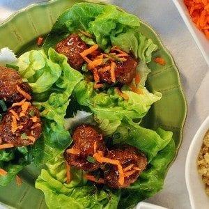 Six teriyaki meatballs sprinkled with shredded orange carrots on butter leaf lettuce on a green plate