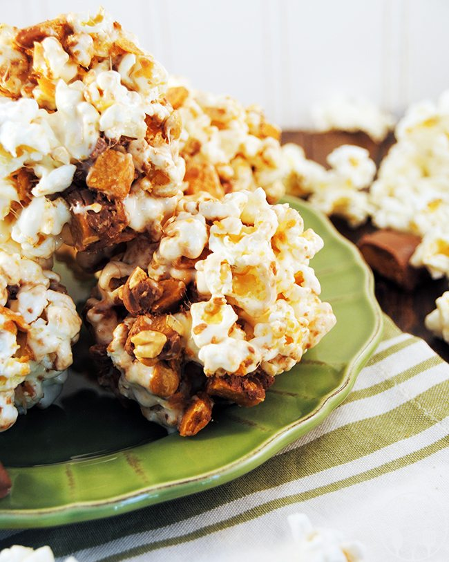 Candy Marshmallow Popcorn Balls - Good old fashion candy marshmallow popcorn balls made using kettle popcorn, melted marshmallows, and chopped candy bars added for a salty sweet popcorn ball