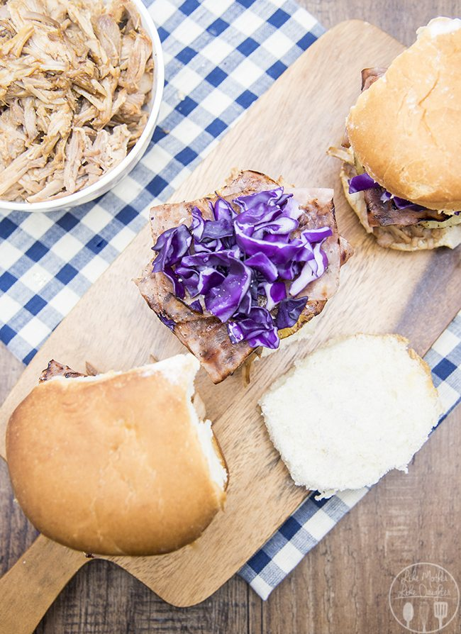 Hawaiian Pulled Pork Sliders - These Hawaiian pulled pork sliders are great for a regular dinner or for game day! They're easy to in the slow cooker and so delicious with tender pulled pork, topped with a sweet pineapple slice, crunchy and salty ham and crispy cabbage.