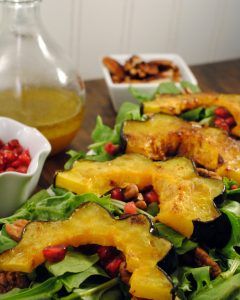 Roasted Autumn Squash Salad with roasted acorn squash, toasted pecan halves, fresh greens, and juicy pomegranate arils served with a warm apple vinaigrette.