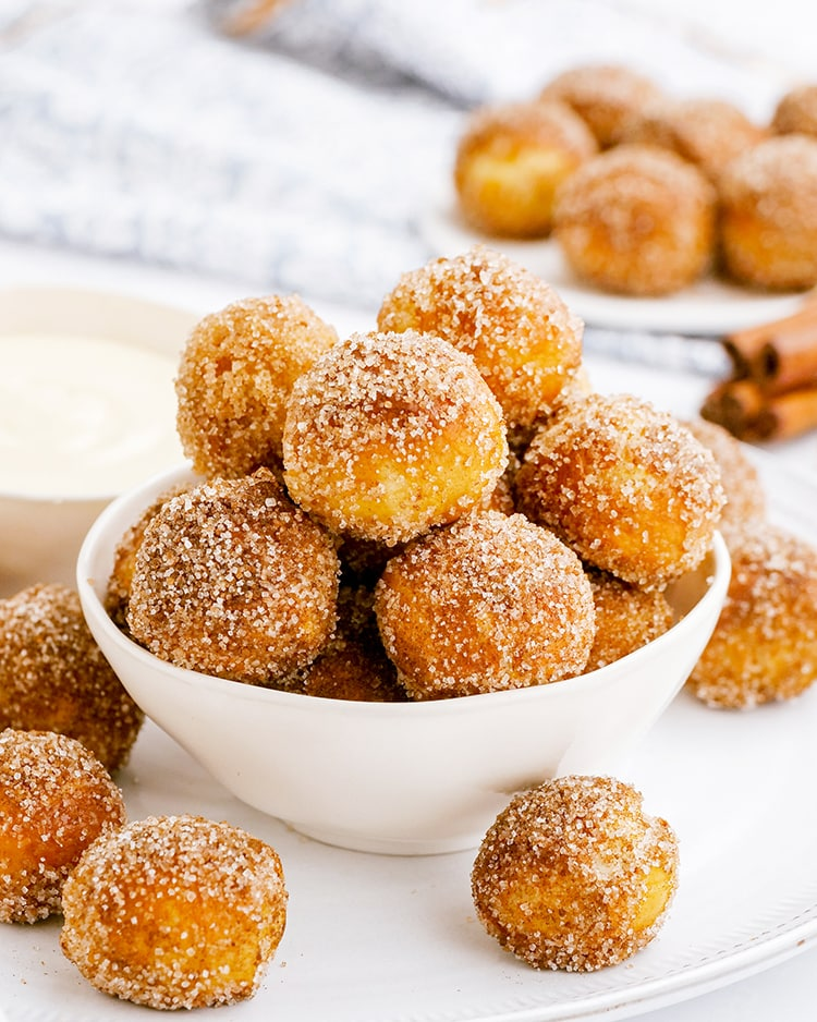 A bowl of cinnamon sugar soft pretzel bites, piled up with a few on the side of the bowl.