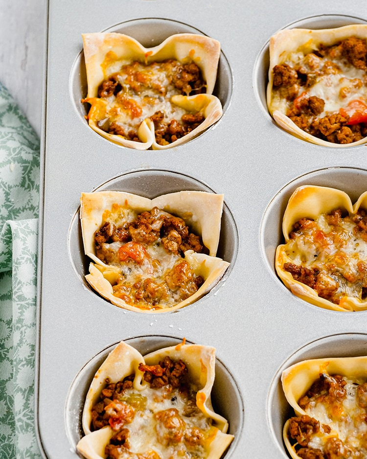 Wonton taco cups in a baking pan, showing a wonton wrapper filled with ground beef, and topped with melted cheese.