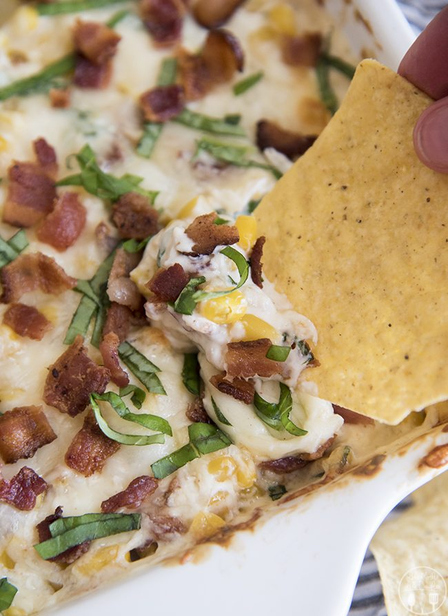 Creamy Corn Dip - This easy and delicious dip is a hot cheesy dip full of sweet corn, cream cheese, crunchy bacon and more. Its perfect for potlucks and parties all summer long!