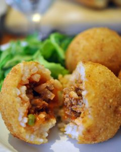 Arancini is authentic Sicilian cuisine - a ragu stuffed rice ball dipped in bread crumbs and fried. Make these and your friends will believe you just became an Italian.