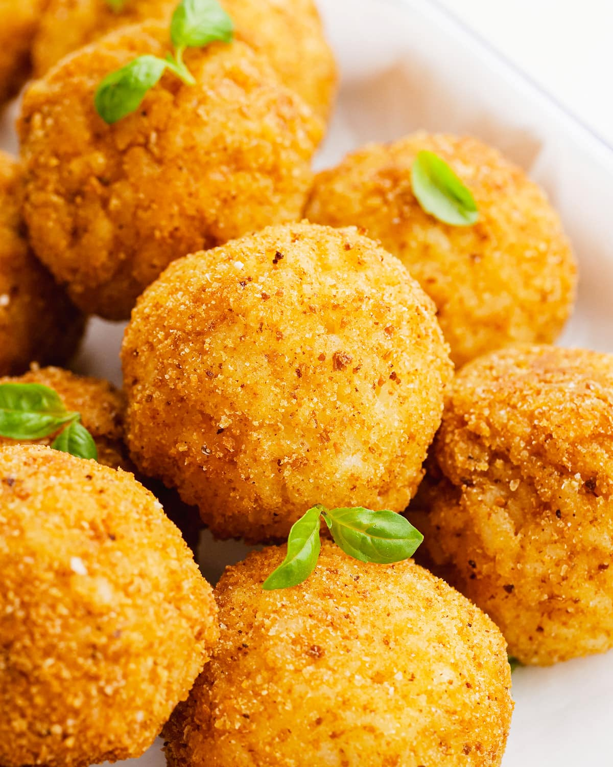 A close up of arancini balls in a pile, with small basil leaves among them.