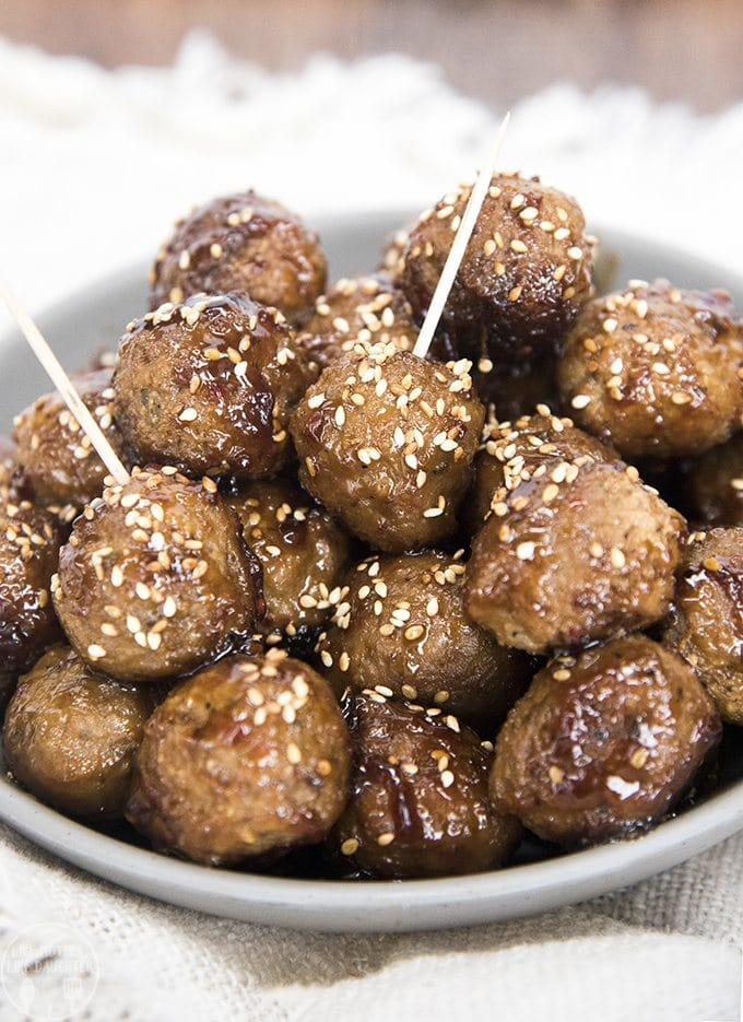 A bowl of teriyaki coated meatballs. Two of the meatballs have toothpicks in them. They are all sprinkled with sesame seeds.