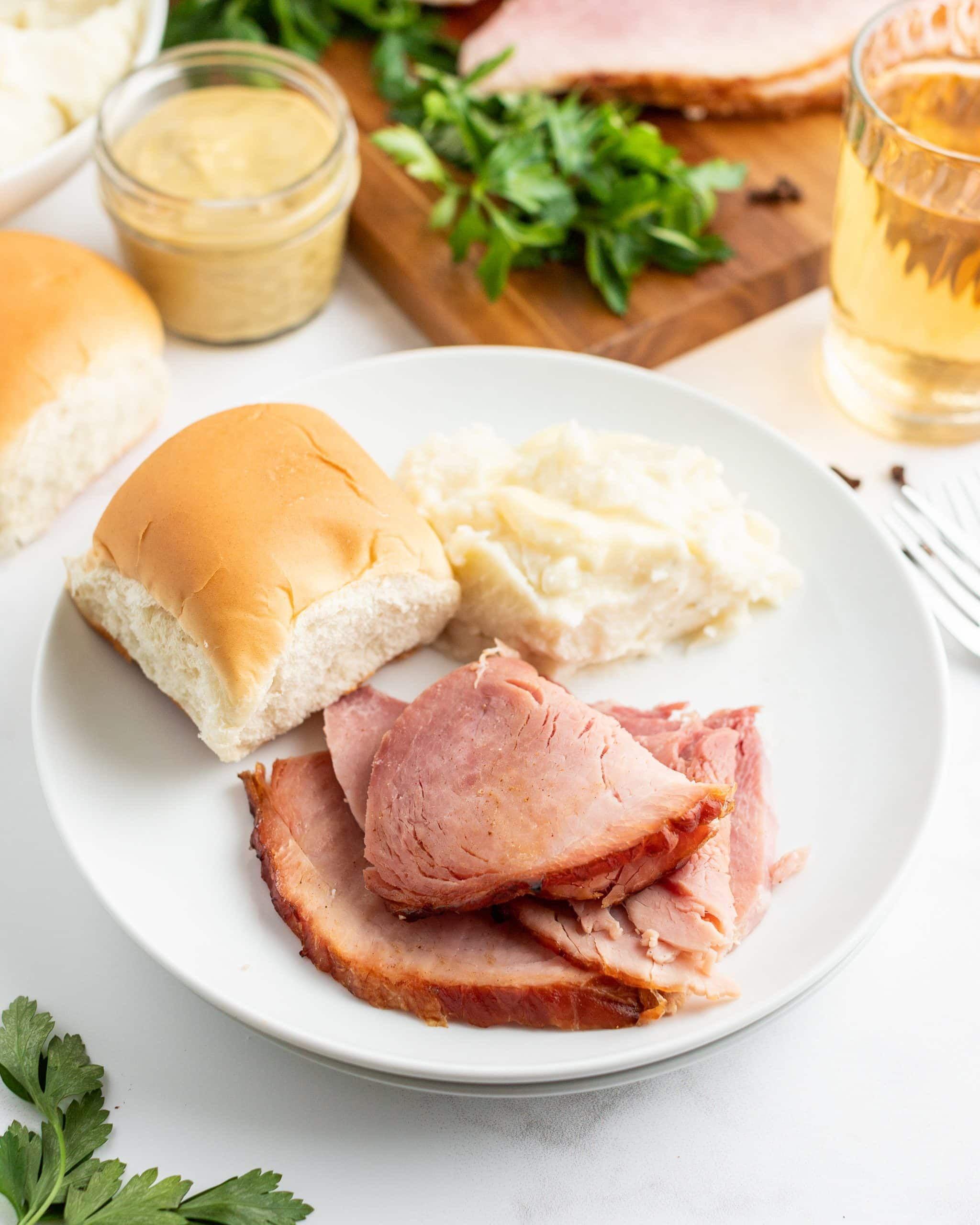 Slices of ham on a dinner plate with a roll and mashed potatoes.