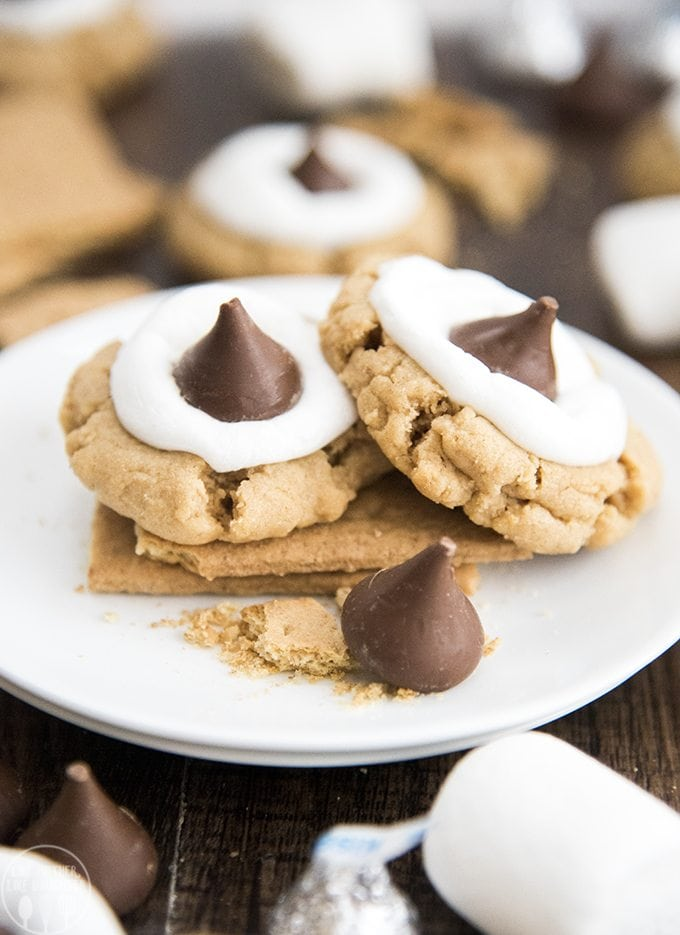 These peanut butter s'mores cookies have a peanut butter graham cracker filled cookie, topped with a gooey marshmallow, and a chocolate Hershey kiss. These cookies combine the great taste of s'mores and peanut butter into a delicious cookie!