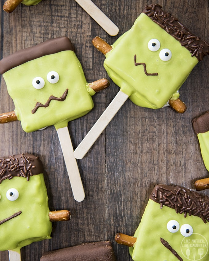 Frankenstein smores pops have marshmallow creme in the middle of two graham crackers and are dipped in chocolate to look just like Frankenstein.
