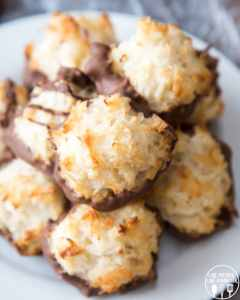 A plate of coconut macaroons, with their bottoms dipped in chocolate. They are lightly golden brown little mounds of coconut.