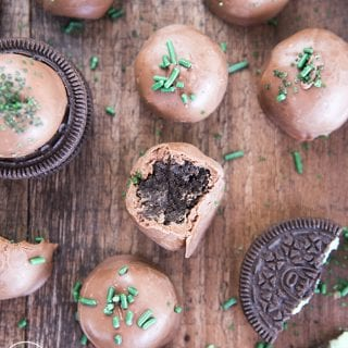 Mint Oreo truffles arranged randomly on a wooden board, with green sprinkles around, and Oreo pieces too. One of the truffles is bitten into to show the Oreo filling in the middle.