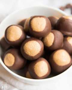 A bowl of peanut butter balls dipped in chocolate up to the top third, that makes them look like buckeye nuts.