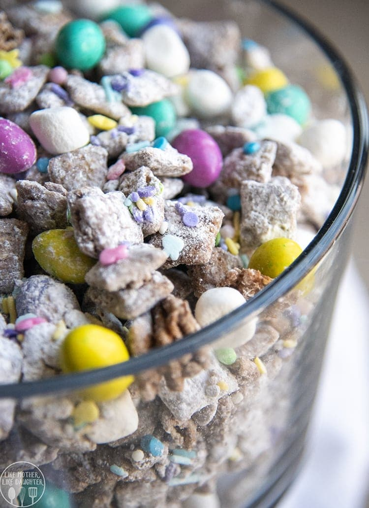These Easter Muddy Buddies are such a fun and tasty Easter treat, with peanut butter chocolate muddy buddies, speckled egg m&ms, marshmallow bunny tails, and spring sprinkles.
